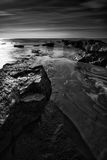 Beautiful black and white landscape of rocky shore at sunset Stock Photo
