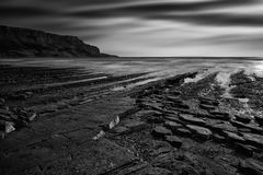 Beautiful black and white landscape of rocky shore at sunset Stock Photos