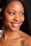Beautiful black woman headshot happy smile. Portrait of beautiful black woman with lovely eyes and cheerful smile, looking away from camera Royalty Free Stock Photo