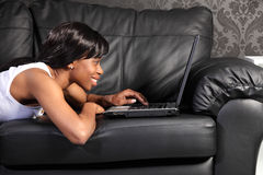 Beautiful black woman at home using facebook stock photography