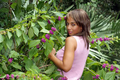 Beautiful Black Woman Outdoors (4). A beautiful mature black woman soaks up some atmosphere amidst colorful, lush tropical vegetation outdoors, looking over her Stock Photos