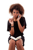 Beautiful black woman on the phone taking notes Stock Photography