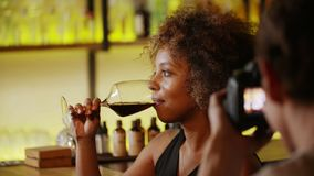 Beautiful black woman on photo session in bar. She drink wine and laughs