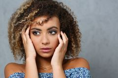 A beautiful black woman portrait. Tests the emotion of bewilderment of fear of terror confusion beauty fashion style mulatto curly hair with white locks eye Stock Photo