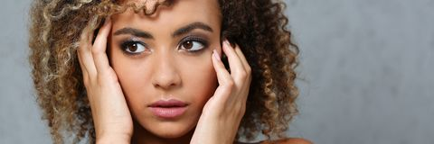 A beautiful black woman portrait. Tests the emotion of bewilderment of fear of terror confusion beauty fashion style mulatto curly hair with white locks eye Royalty Free Stock Photo