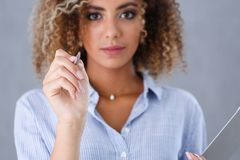 Beautiful black woman portrait. Holds a ballpoint pen in his hand. And points in the fashion vogue style mulatto curly hair with white locks eye view of the Royalty Free Stock Photo