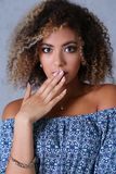 A beautiful black woman portrait.He opens her mouth. With her hand and says uops beauty fashion style mulatto curly hair with white locks eye view of the camera Royalty Free Stock Image