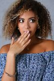 A beautiful black woman portrait. He opens her mouth with her hand and says uops beauty fashion style mulatto curly hair with white locks eye view of the camera Royalty Free Stock Image