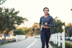 Beautiful dark skinned girl running on a path in a city park Royalty Free Stock Photos