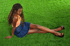 A Beautiful black woman sitting on grass. A beautiful black woman with long legs and long hair sits on the grass and crosses her legs Stock Photos