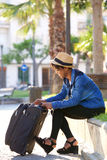 Beautiful black woman sitting outside with suitcase Royalty Free Stock Photos