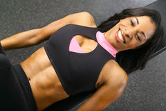Beautiful Black Woman Smiling On Bench. Smiling african american woman training or exercising in gym, laying on bench Royalty Free Stock Photo