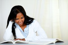 Beautiful black woman smiling and reading a book Royalty Free Stock Image