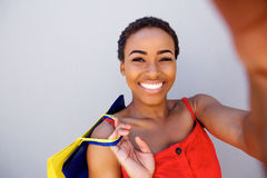 Beautiful black woman smiling with shopping bags taking a selfie Royalty Free Stock Image