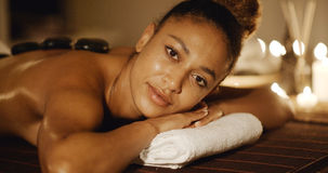 Beautiful Black Woman At Spa. Young african-american woman getting spa treatment with hot stone massage stock photo