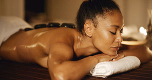 Beautiful Black Woman At Spa. Young african-american woman getting spa treatment with hot stone massage royalty free stock images