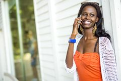Beautiful black woman talking on phone and smiling. During a summer day Stock Photos