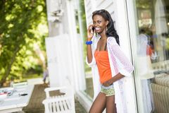 Beautiful black woman talking on phone and smiling. During a summer day and her reflection showing on the window Stock Photography