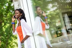 Beautiful black woman talking on phone and smiling. During a summer day and her reflection showing on the window Royalty Free Stock Images