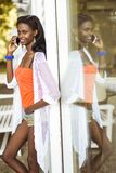 Beautiful black woman talking on phone and smiling. During a summer day and her reflection showing on the window Stock Photo