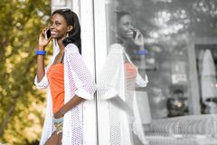 Beautiful black woman talking on phone and smiling. During a summer day and her reflection showing on the window Royalty Free Stock Photos