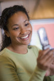 Beautiful black woman texting on cell phone. Smiling African American woman text messaging on cell phone Royalty Free Stock Photos
