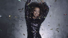 Beautiful black woman throwing golden confetti, slow motion . Afro american woman dancing among confetti over silver background