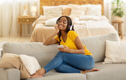 Free Beautiful Black Woman With Mobile Phone And Headphones Sitting On Comfy Sofa And Listening To Music At Home Stock Images - 196399874