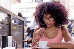 Beautiful black young student tourist woman with glasses sitting outdoors drinking a cup of coffee in Sao Paulo during summer, stock photos