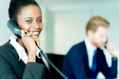 A beautiful, black, young woman working at a call center in an o. A beautiful, black, young women working at a call center in an office with her red haird stock images