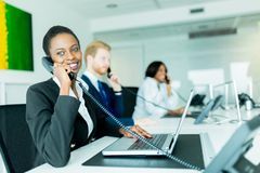 A beautiful, black, young woman working at a call center in an o. A beautiful, black, young women working at a call center in an office with her red haird stock photography