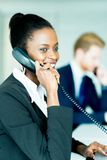 A beautiful, black, young woman working at a call center in an o. A beautiful, black, young women working at a call center in an office with her red haird stock photo