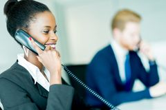 A beautiful, black, young woman working at a call center in an o stock photo