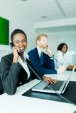 A beautiful, black, young woman working at a call center in an o Stock Photography