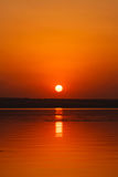 Beautiful blazing sunset landscape at the river Dnipro and orange sky above it with awesome sun golden reflection on calm water Stock Photos