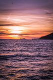 Sunset in Marina di Carrara. Beautiful blazing sunset in mediterranean sea landscape and orange sky above it with awesome sun golden reflection on calm royalty free stock photography