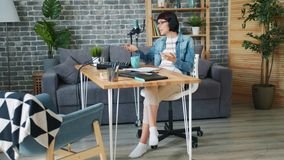 Beautiful blogger in headphones recording podcast speaking in microphone at home. Beautiful young woman blogger in headphones is recording podcast speaking in stock footage