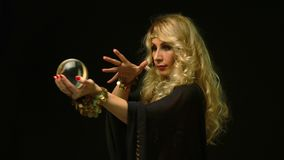 Beautiful blond astrologer woman looking through crystal ball.