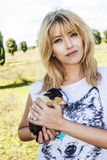 Beautiful blond blue eyes with Peruvian guinea pig animal. A beautiful blond woman with blue eyes is holding in her arms a sweet Peruvian guinea pig. The woman royalty free stock image