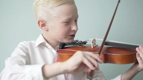 Beautiful blond boy plays the violin. In a lesson at a music school stock footage
