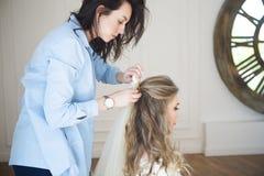 Beautiful bride having hairdo in her wedding day. Beautiful blond bride having hairdo in her wedding day stock photo