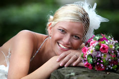 Beautiful blond bride holding bouquet royalty free stock photography