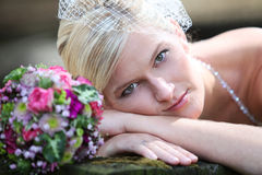 Beautiful blond bride holding bouquet Stock Images