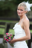 Beautiful blond bride holding bouquet Stock Photos