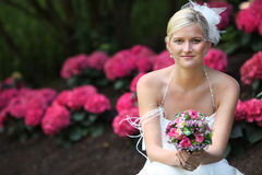Beautiful blond bride holding bouquet stock image