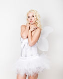 Beautiful blond bride wearing white dress with professional make-up and hairstyle, wings behind Royalty Free Stock Images