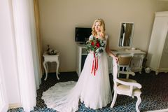 Beautiful blond bride with wedding bouquet in the luxurious apartments.  stock photo