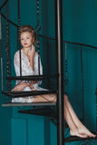 Beautiful blond bride in white negligee sitting on the black wrought iron stairs. Beautiful blond bride in white negligee sitting on the black wrought iron Royalty Free Stock Photos