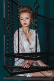 Beautiful blond bride in white negligee sitting on the black wrought iron stairs. Beautiful blond bride in white negligee sitting on the black wrought iron Stock Images