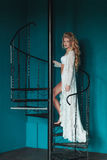 Beautiful blond bride in white negligee walking up black wrought iron staircase.  Stock Photos